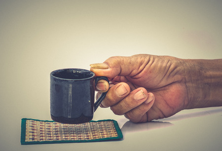 Old Man hand hold with black cup on the white table