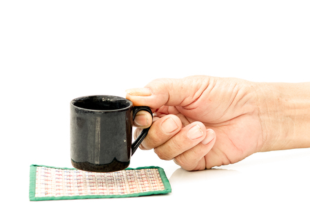 Old Man hand hold with black cup on the white table 写真素材 - 124719845