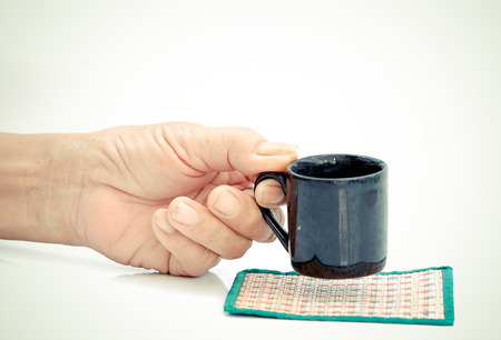 Old Man hand hold with black cup on the white table 写真素材 - 124719863