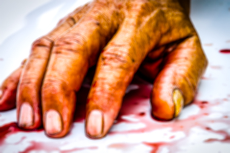Blurry of bloody hand on the table. a violence or fear horror concept.