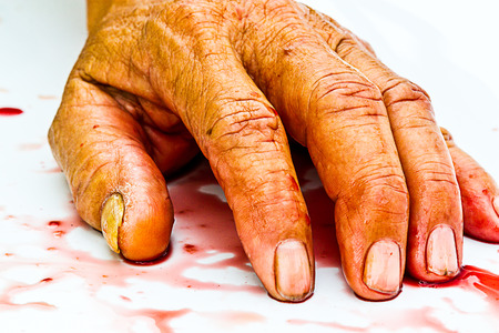 bloody hand on the table. a violence or fear horror concept. Reklamní fotografie
