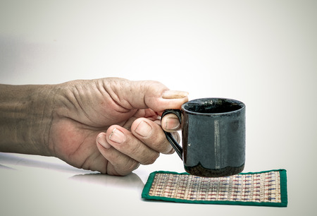 Old Man hand hold with black cup on the white table 写真素材 - 124720162