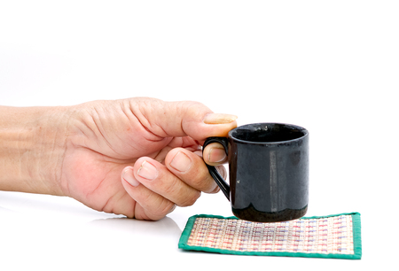 hand hold with black cup on the white table