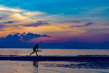 Silhouette of man with surfboard on the beach with twilight sky background