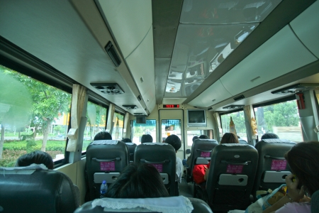 tourists stop:  inside of a bus with passenger sitting in the seats  Stock Photo