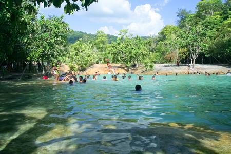 KRABI, THAILAND - OCTOBER  29 2011: Tourist play water in Sra Morakot (Emerald Pool). Photo at Krabi Province, Thailand.