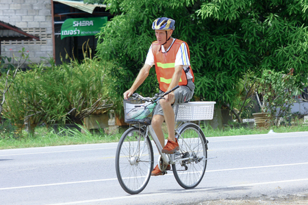 CHIANGMAI, THAILAND -OCTOBER 6 2014: Old man on bicycle. Photo at road no.121 about 8 km from downtown Chiangmai, thailand.