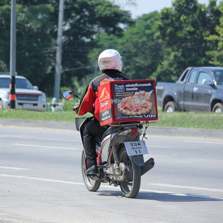 CHIANGMAI, THAILAND -OCTOBER  18 2015:  Delivery service man ride a Motercycle of Pizza Hut Company. Photo at road no.1001 about 8 km from downtown Chiangmai, thailand. Banco de Imagens - 48944763