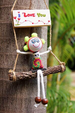 i love u: Word i Love u on white wood baord with doll on Palm tree background