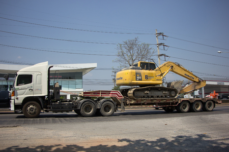 delivery truck: CHIANG MAI, THAILAND -FEBRUARY 27 2017:  Private Komatsu backhoe on truck. On road no.1001 8 km from Chiangmai city.