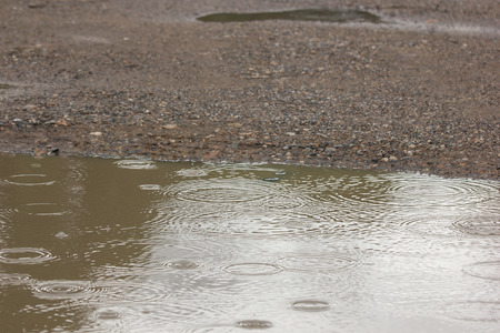 water puddles with raindrops and water circles on cracked wet  road Stock Photo