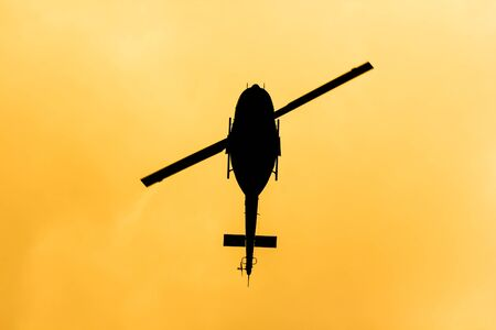 Black Helicopter flying in the orange sky