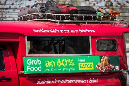 Chiangmai, Thailand - February 7 2020: Grab Food Advertise on Red taxi chiang mai. Car On road no.1001 8 km from Chiangmai Business Area. Editorial