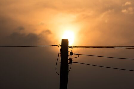 Closeup Sunset and Eletricity line and electricity post wtih blue sky background