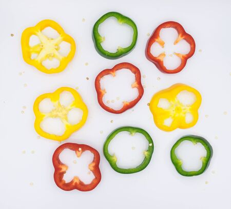Set of sliced green yellow and red bell pepper section pieces isolated over white background, view above