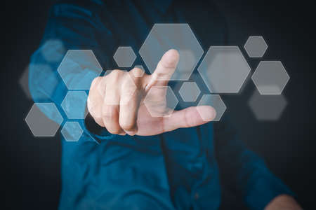 The man shows the gesture of pointing touching on the virtual screen and has a beehive screen effect.  Investment ideas, business concepts, technology concepts.