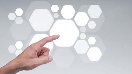 The man shows the gesture of pointing touching on the virtual screen and has a beehive screen effect.  Investment ideas, business concepts, technology concepts