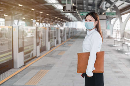 An Asian woman wearing a mask stands in queue waiting for the railcar in the subway. Social Distancing to Prevent Covid 19 Outbreak. Travel concept by railcar. The idea of a businesswomen.