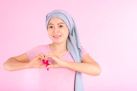 Muslim woman wearing a hijab with a ribbon on her chest shows prevention of breast cancer. On a pink backdrop, breast cancer concept, cancer prevention concept. Stock Photo