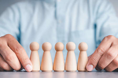 Businessman wearing a blue shirt, arranging the empty wooden blocks with his hands. Which is placed on a white wooden table. Business strategy and action plan. Copy space.