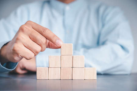 Businessman wearing a blue shirt, arranging the empty wooden blocks with his hands. Which is placed on a white wooden table. Business strategy and action plan. Copy space. Фото со стока