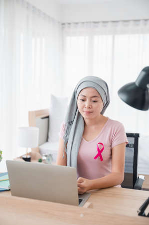 Young Asian woman wearing a hijab uses smartphone and laptop at her desk. Attaching a pink ribbon represents recovery from a cancer patient. Breast cancer concept, cancer prevention concept.