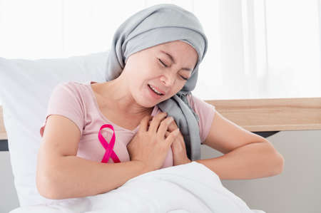 Young asian women wearing hijab Hands held on the chest due to pain while sitting in bed. Indicates recovery from cancer Breast cancer concept, cancer prevention concept.