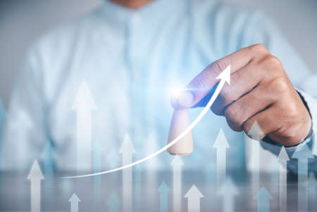 Businessman graphs how the arrow grows up On a high-tech blue background transparent screen Ideas, goals, develop plans for success and strategies.