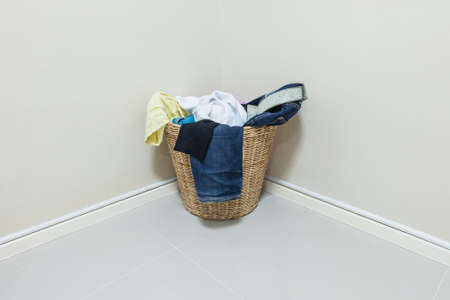 used clothes: Closeup used clothes in wood basket at corner in room