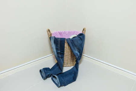 used clothes: Used clothes in wood basket at corner in room