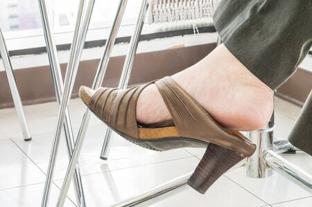 trouser legs: Closeup foot with old high heel shoes of woman officer