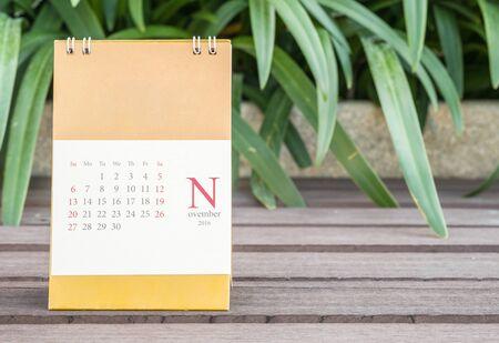 Closeup cute calendar in november on blurred garden view background