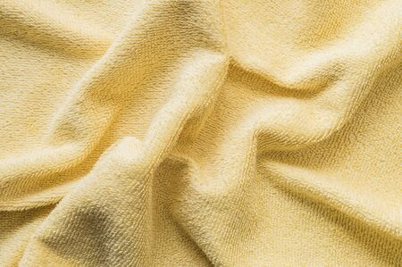 tatter: Closeup wrinkled yellow napkin fabric background