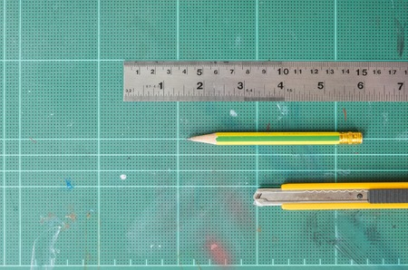 wood cutter: Cutter , wood pencil and ruler on old green rubber pad background
