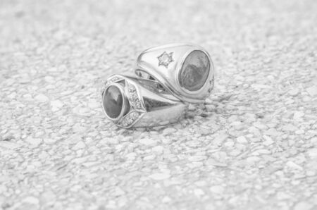 diamond rings: Closeup old diamond rings on blurred stone floor background in black and white tone