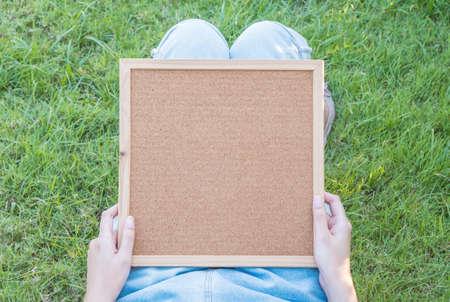 lied: Closeup cork board on body of woman lied on grass floor