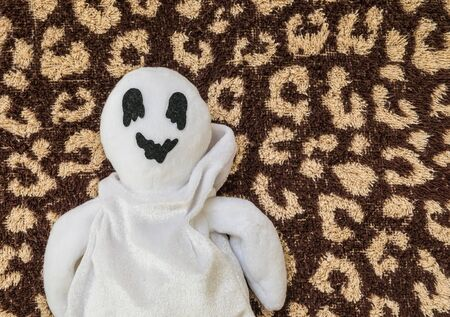 horrific: cute ghost doll on brown fabric background Stock Photo