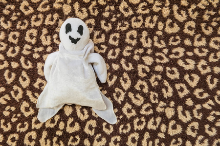 unwanted: cute ghost doll on brown fabric background Stock Photo