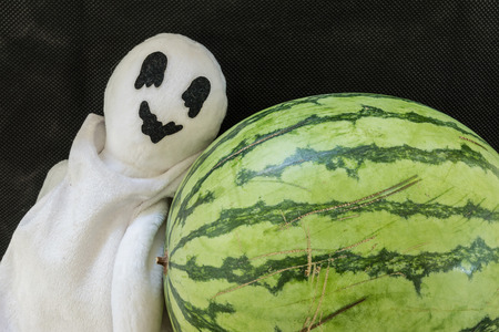 wraith: cute ghost doll with watermelon on black fabric background Stock Photo
