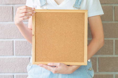 declare: Closeup cork board in hand of woman in front of body