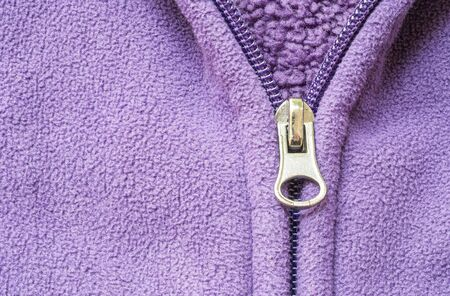tatter: Closeup head of zipper at purple jacket textured background Stock Photo
