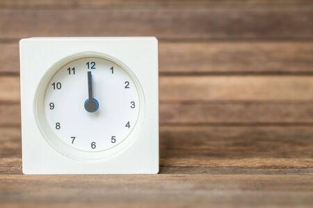 showed: Closeup white clock showed twelve oclock on blurred brown wood board background