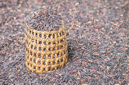 nutrientes: Primer plano de la pila de arroz negro llamado arroz riceberry con mimbre de madera, arroz con altos nutrientes en fondo enmascarado de textura riceberry