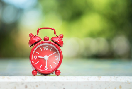 fifteen: Closeup red alarm clock display seven hours and fifteen minutes on screen on blurred marble desk and park view background