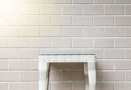 wall light: Closeup wood weave table on blurred brown brick wall texture background with sun light , beautiful interior in relaxation of house concept