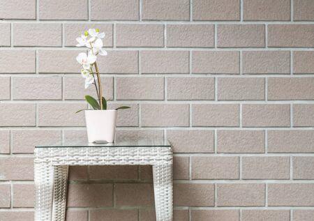 orchid house: Closeup artificial plant with white orchid flower on pink flower pot on wood weave table on blurred brown brick wall texture background , beautiful interior in relaxation concept of house Stock Photo
