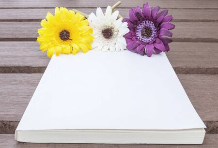 faked: Closeup white note book with colorful faked flower on blurred old wood table textured background