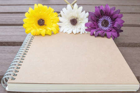 faked: Closeup brown note book with colorful faked flower on blurred old wood table textured background