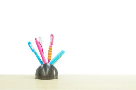 desk tidy: Closeup color pen with black ceramic desk tidy for pen on blurred wooden desk isolated on white background Stock Photo
