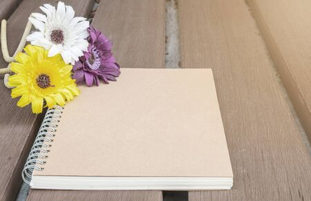 Closeup brown note book with colorful faked flower on blurred old wood table textured background
